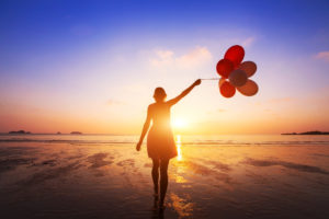 Woman Letting Go of Balloons at Beach